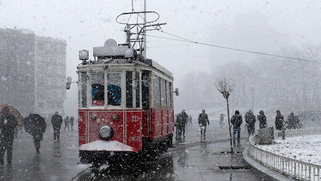 People walk by a tram near Gezi Park on Taksim Square during a snowy day in Istanbul, Feb. 17, 2015.