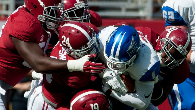 Middle Tennessee's Shane Tucker is gang tackled by Alabama linebacker Reggie Ragland (19), defensie back Geno Matias-Smith (24) and linebacker Denzel Devall (30) and defensive lineman Dalvin Tomlinson (54) at Bryant-Denny Stadium in Tuscaloosa, Ala. on Saturday September 12, 2015. (Mickey Welsh / Montgomery Advertiser)