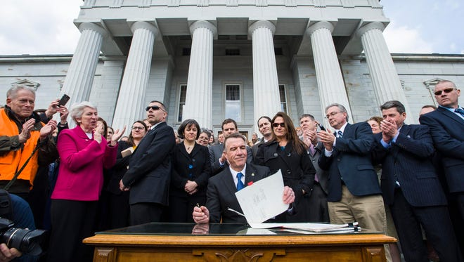 Gov. Phil Scott signs three gun reform bills on the steps of the Statehouse in Montpelier on Wednesday , April 11, 2018.