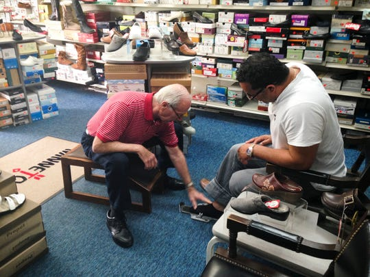 Ed Davis, 76, owner of The Shoe Horn in Medford, sizes up customer Sharon Merhavi for a pair of shoes. Davis has been selling footwear since he was 15, and has owned stores in Burlington County for the last 43 years.
