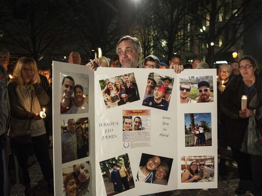 In this Feb. 20, 2017 photo, tears fill the eyes of Jeff James, father of missing Duquesne University grad student Dakota James, who vanished from Downtown after a night out with friends, as he holds a board covered in photos of his son during a vigil at Katz Plaza in downtown Pittsburgh. As the anniversary of James' death approaches, both families and Pittsburgh police still do not know what happened. (Stephanie Strasburg/Pittsburgh Post-Gazette via AP)