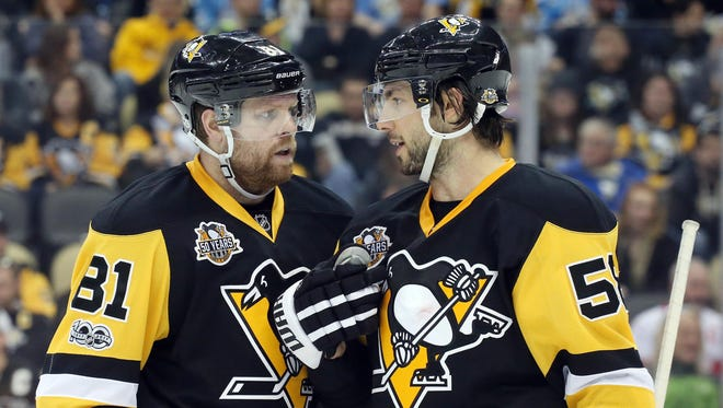 The Pittsburgh Penguins' Phil Kessel (left) and Kris Letang (right) chat before a faceoff this season. The Penguins will be without Letang in the playoffs.