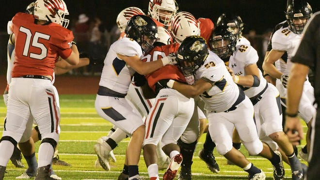 Stephenville's Corbin Poston (9), Damian Meza (53) and Reese Young (42) combine on a tackle during Friday's non-district football game in Melissa.