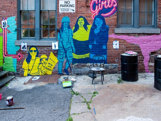 Emily Herr, left, and Sarah Apple paint a mural in