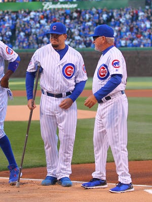 Chicago Cubs left fielder Kyle Schwarber (left) and manager Joe Maddon (right) prior to a game against the Cincinnati Reds at Wrigley Field.