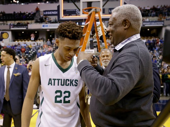 Oscar Robertson looks to put the winning medal around Crispus Attucks' Nike Sibande (22) after winning the IHSAA 3A Boys Basketball State Finals game Saturday, at Bankers Life Fieldhouse.