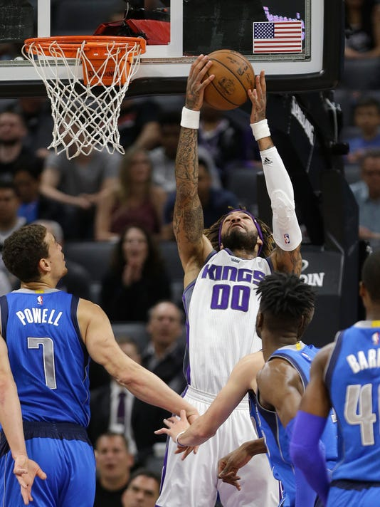 Sacramento Kings center Willie Cauley-Stein, center, grabs the ball between Dallas Mavericks' Dwight Powell, left, and Nerlens Noel, second from right, during the first half of an NBA basketball game Tuesday, April 4, 2017, inSacramento, Calif. (AP Photo/Rich Pedroncelli)