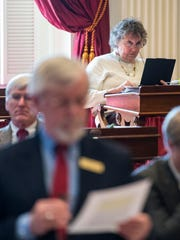 Rep. Alice Miller, D-Shaftsbury (right), works on her computer at the Statehouse in Montpelier on Tuesday as Rep. Steve Carr, D-Brandon (left), explains a bill to create a division on telecommunications and connectivity within the Department of Public Service.