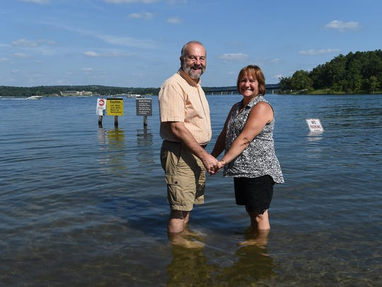 Bob Lelly holds hands with his wife, Patty, on Thursday at the old landing site for the Norfork Lake ferry. The Bellville, Ill., couple were in the area for the weekend to celebrate the 35th anniversary of being married on the ferry Aug. 8, 1980.