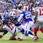 New York Giants wide receiver Dwayne Harris (17) dives in for a touchdown on a reception on a pass from quarterback Eli Manning as Buffalo Bills strong safety Bacarri Rambo (30) defends during the first half of an NFL football game, Sunday, Oct. 4, 2015, in Orchard Park, N.Y. Giants' Odell Beckham (13) and Bills' Corey Graham (20) look on during the play.