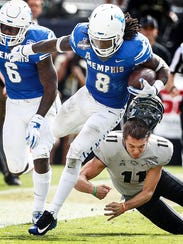 Memphis kick returner Darrell Henderson (left) runs