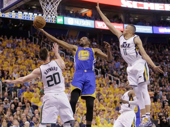 Golden State Warriors forward Kevin Durant (35) lays the ball up as Utah Jazz's Gordon Hayward (20) and Dante Exum (11) defend in the first half during Game 4 of the NBA basketball second-round playoff series, Monday, May 8, 2017, in Salt Lake City. (AP Photo/Rick Bowmer)