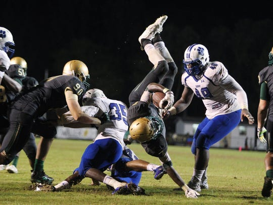 Lincoln running back Ricky Henrilus gets upended as he tries to reach the goal line. Henrilus rushed for 214 yards and 4 touchdowns in the Trojans' 42-34 win over Godby.