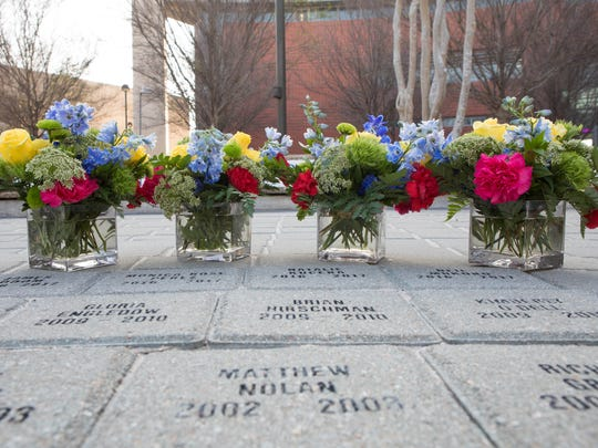 Flowers lay in front of four new bricks with the names of Texas A&M University-Corpus Christi students who died this past year. The names were added to the Islander Tribute memorial during a ceremony Tuesday, April 4, 2017.