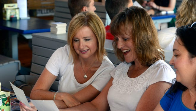 Melissa Adams Webb, Krista Verge and Carrie Disouryavong look at familt photos during their get together Saturday, May 13, 2017 at Flounders Pensacola Beach. The group of  moms who met at the hospital 18 years ago when their babies were born, have developed a friendship and have been meeting regularly since then.