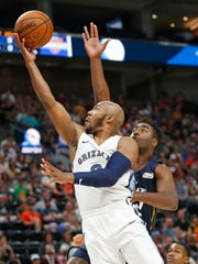 Grizzlies guard Jevon Carter, left, lays the ball up as Jazz forward Kelan Martin, rear, defends during the first half Tuesday.