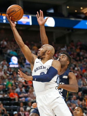 Memphis Grizzlies guard Jevon Carter, left, lays the ball up as Utah Jazz forward Kelan Martin, rear, defends during the first half of an NBA summer league basketball game Tuesday, July 3, 2018, in Salt Lake City.