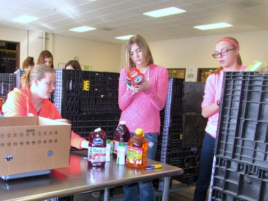 Volunteers sort donated food Monday at the Food Bank