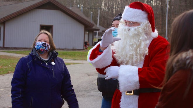 Dressed as Santa Claus, Eric Wakefield signs with a guest Saturday, Dec. 5, during the Deaf and Hard of Hearing Services' Signing with Santa event in Comstock Park.