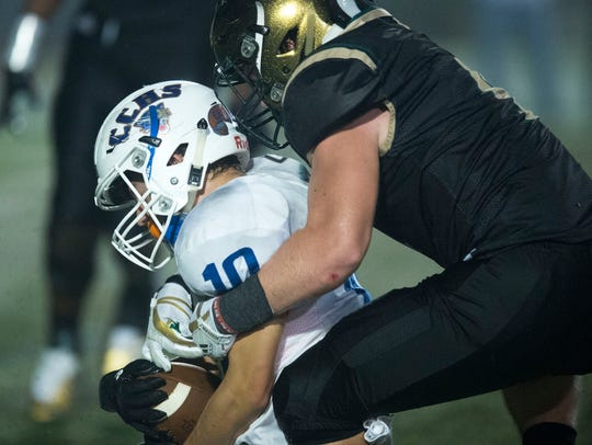 Campbell County's Justin Nelson is tackled by Catholic's