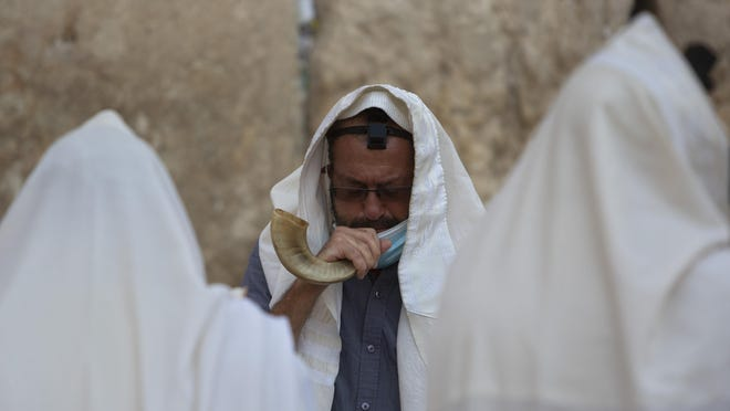 An ultra-Orthodox Jewish man blows a shofar, a musical instrument made from an animal horn, as he prays on Wednesday ahead of the Jewish new year at the Western Wall, the holiest site where Jews can pray in Jerusalem's old city.