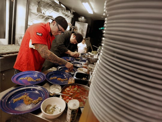 Sous Chef Josh Baray and Chef Robert Garay plate the salad course Wednesday night at Dark Horse Tavern.