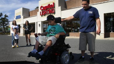Mike Roman and Damarius Roman at Capitol Lighting store in Eatotown. Capitol Lighting donated a van to the family for their son Damarius who has muscular dystrophy.Eatontown,NJ. Thursday, May 12,2016.Noah K. Murray-Correspondent/Asbury Park PressASB 0513 Damarius Van