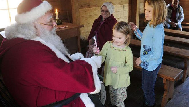 Father Christmas listens to the holiday wishes of young visitors during the one of the annual Christmas in the Backcountry events at the Living History Park in North Augusta. This year's event has been canceled because of COVID-19 restrictions.