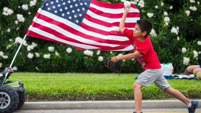 Aaron Campos Jr., 8, plays catch with his father before the City of Corpus Christi Mayor's Big Bang Celebration parade on Wednesday , July 4, 2018 on Shoreline Boulevard.