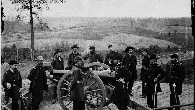 In this 1864 photo provided by the Library of Congress, Gen. William T. Sherman, leans on breach of gun, and staff at Federal Fort No. 7, in Atlanta. On Nov. 16, 1864, Sherman watched his army pull out of Atlanta, and marched with 62,000 veteran troops to the Atlantic coast at Savannah, conquering territory and making a point to the enemy in what would be known as Sherman's March to the Sea during the American Civil War.