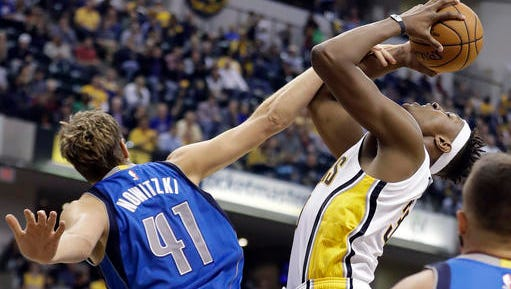 Indiana Pacers' Myles Turner is fouled by Dallas Mavericks' Dirk Nowitzki as he goes up of a shot during the second half of an NBA basketball game Wednesday.