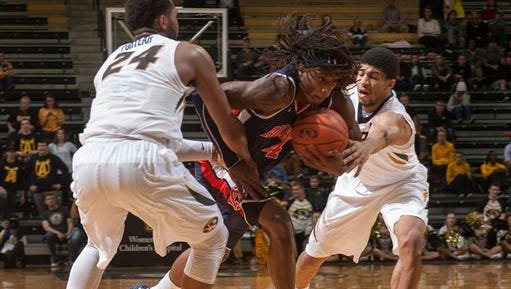Auburn's T.J. Dunans, center, fights his way between Missouri's Jordan Barnett, right, and Kevin Puryear, left, during the second half of an NCAA college basketball game Tuesday, Jan. 10, 2017, in Columbia, Mo. Auburn won the game 77-72.