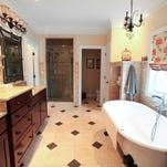 The master bathroom in the home of Mary and Charlie Brown in Prospect has Roman shades and double vanity with tower cabinet in the middle with mirrors and modern lighting. March 3, 2015