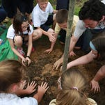 """Director of Urban Conversation for Louisville, Chris Chandler, top right, helps pack dirt with students from St. Aloysius school during the City of Pewee Valley's Environmental Education Day. """"There's just benefits of getting exposed to dirt, to trees and to nature,"""" Chandler said. May 5, 2015"""