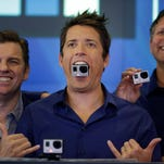 GoPro's CEO Nick Woodman holds a GoPro camera in his mouth as he celebrates his company's IPO at the Nasdaq MarketSite in New York, Thursday, June 26, 2014.