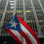 The Puerto Rican flag flies as people protest outside of Wall Street against cutbacks and austerity measures forced onto the severely indebted island of Puerto Rico on Dec. 2, 2015 in New York City. Spencer Platt/Getty Images