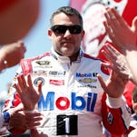 Sprint Cup Series driver Tony Stewart high fives fans during driver introductions prior to the Toyota Owners 400 at Richmond International Raceway, his first race of the season.