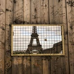 The Eiffel Tower in Paris through a grill in wooden panels surrounding a construction site, May 15, 2016.