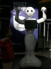 This Thursday, Dec. 22, 2016, photo, shows Pepper the robot at Westfield Mall in San Francisco. While merrily chirping, dancing and posing for selfies, Pepper looks like another expensive toy in the San Francisco mall where it will be entertaining shoppers through mid-February. But it would be a mistake to dismiss Pepper as mere child's play, even though kids flock around the 4-foot-tall humanoid as it speaks in a cherubic voice that could belong to either a boy or girl.