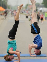 Evansville Power Yoga instructor Damon Murray, right, works on an inversion pose with student Samantha Minnette, left, during the Evansville Streets Alive Festival on Fulton Avenue in 2013.