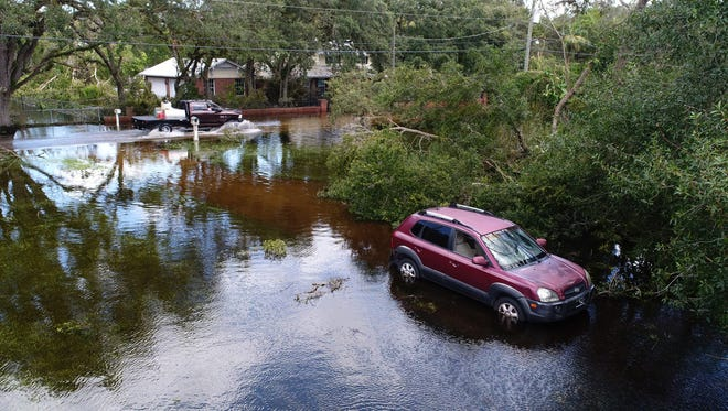 A car sits in a flooded driveway as cars pass on the road Tuesday, Sept. 12, 2017, two days after hurricane Irma passed through the Lehigh Acres area outside Fort Myers, Fla.
