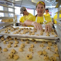 Kaitlyn Anderley, 17, packs orders of cheese curds to order at The Mouth Trap Cheese Curds booth in the Food Building of the Minnesota State Fair.