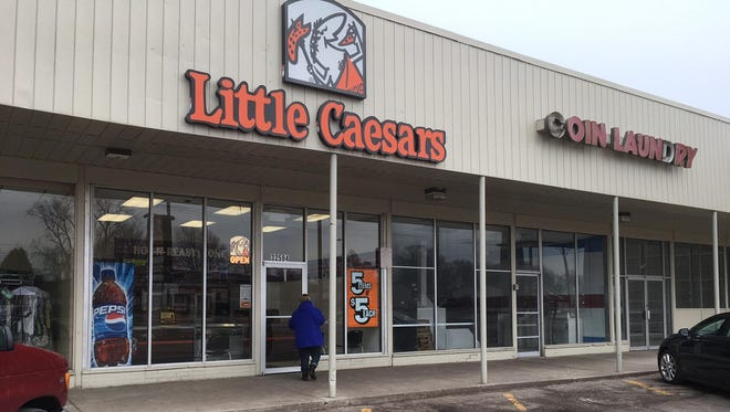A day after the passing of founder Mike Ilitch, a customer stops in at the original Little Caesars store in Garden City. It's on Cherry Hill Road between a dry cleaner and a defunct coin laundry.