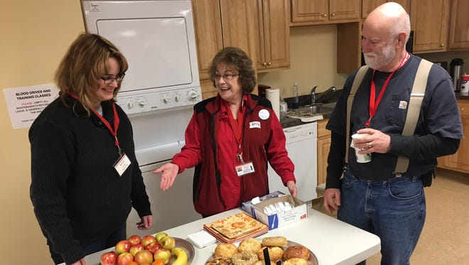 Red Cross Disaster Action Team Members Linda Welsh, Jeri Hague and David Shelp chat at the Red Cross warming center in Howell, where they saw a steady stream of residents coming in for food and warmth during the widespread power outage.