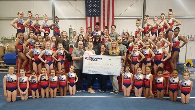 Owners Amy Middlekauff, Lisa Battavio, Lori Carroll-Rieger and Clint Carroll along with the coaches and gymnasts of Star Bound Gymnastics Academy present a donation of $25,000 to Jenna Bundy from the Children's Hospital of Philadelphia for the hospital's Child's Life Fund. The donation represents funds raised through the academy's Star Struck Invitational in Atlantic City and from Bob and Rebecca Mancino of Mancino Manufacturing and Plum Leotards.