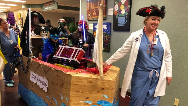 Janice Ryan, surgery department director, leads her team and their specially designed pirate ship float in the sixth annual Mardi Gras parade at Women's & Children's Hospital Friday, Feb. 9, 2018.