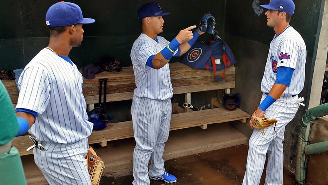 Arismendy Alcantara, Javier Baez, and Kris Bryant chat before a game in Des Moines in 2014.