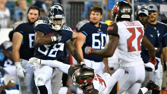 Titans running back Akrum Wadley (38) breaks a tackle by Buccaneers defensive back Marko Myers (38) in the fourth quarter of a preseason game at Nissan Stadium Saturday, Aug. 18, 2018, in Nashville, Tenn.
