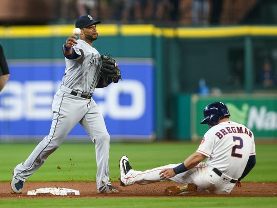 Houston Astros third baseman Alex Bregman is out at second base as Seattle Mariners second baseman Robinson Cano throws to first base to complete a double play during the second inning at Minute Maid Park.