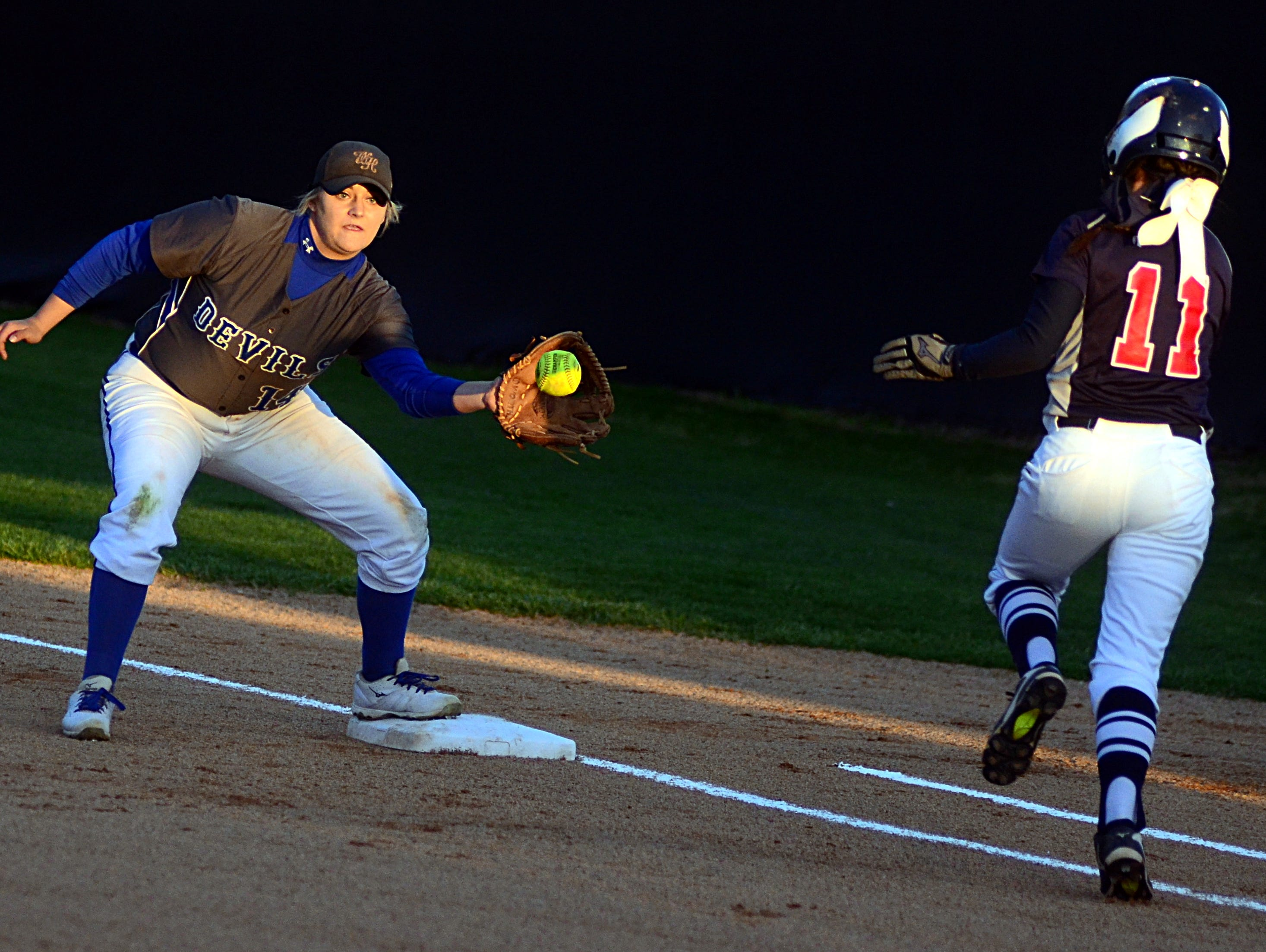 White House High junior Katy Gut receives a throw at first base as White House Heritage's Riley Hallum runs down the first-base line during first-inning action.